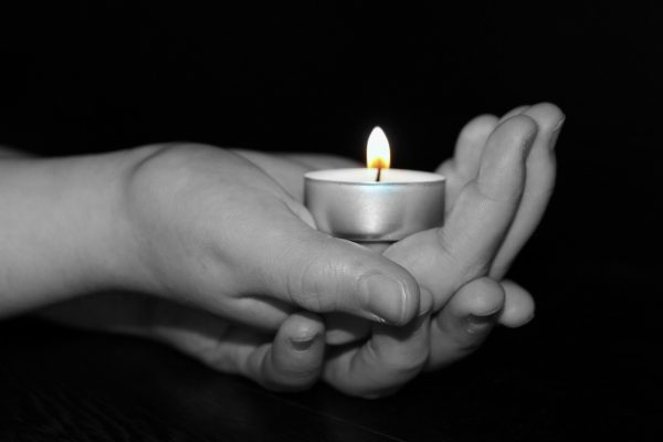 hands cradling a tealight